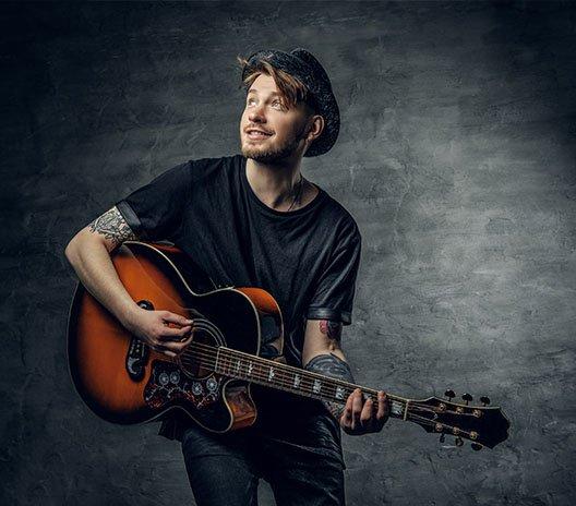artist development guy holding guitar